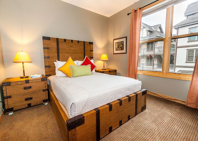 The master suite features a queen-sized bed and a flat screen TV.