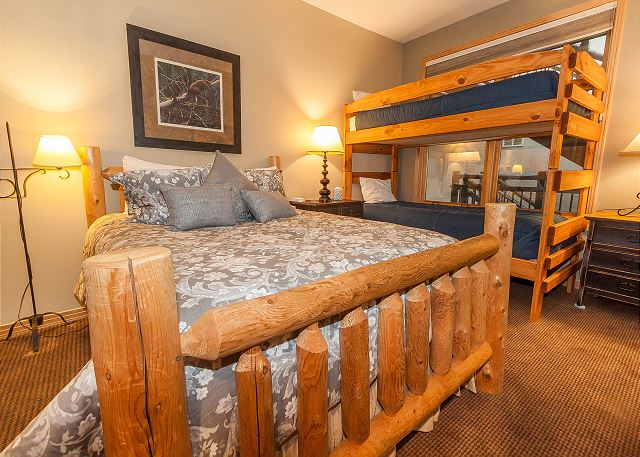 The guest bedroom features a queen-sized bed and a twin-sized bunk bed.