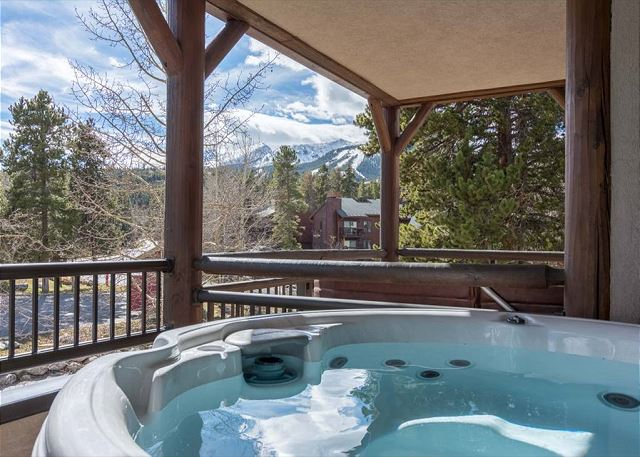 The deck features a private hot tub and a gas grill.