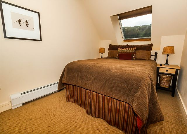 The bedroom features a queen-sized bed and a flat screen TV.