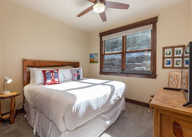 The second guest bedroom is upstairs and features a king-sized with Ivory White Bedding and a mounted flat screen TV.