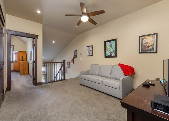 The loft on the third level features a flat screen TV and a queen-sized sleeper sofa.