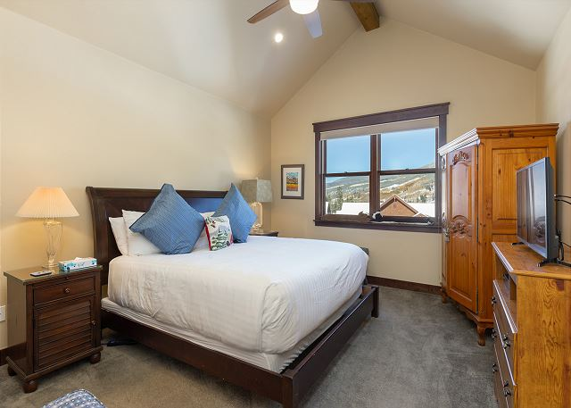 The master bedroom is on the third level and features a king-sized bed with Ivory White Bedding and a flat screen TV.