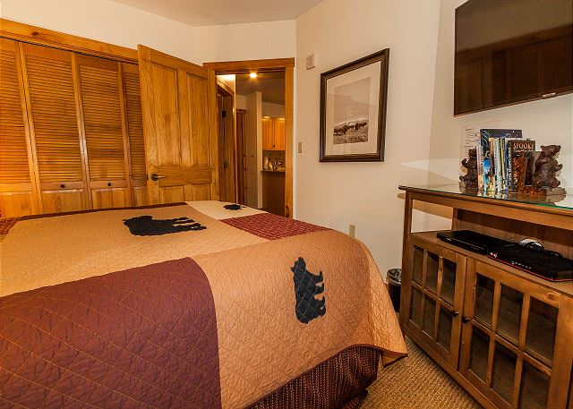 The bedroom features a queen-sized bed and a mounted flat screen TV.