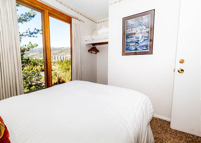 The first guest bedroom features a full-sized bed with Ivory White Bedding.