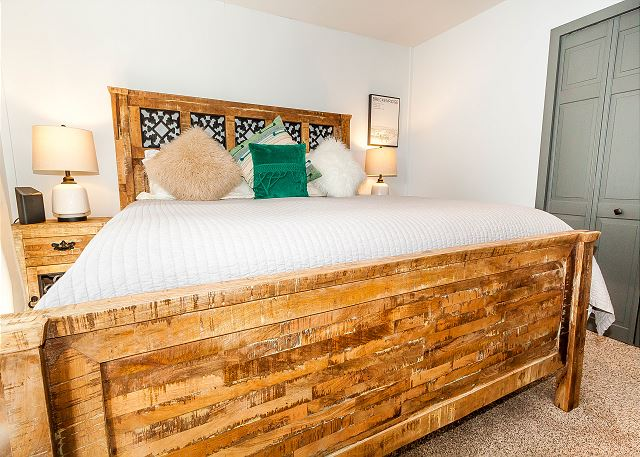 The first guest bedroom is on the first level and features a king-sized bed, a mounted flat screen TV and its own access to the deck.