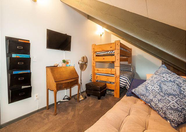 The upstairs loft is the third guest bedroom and features a twin-over-full bunk bed, a futon and a mounted flat screen TV.