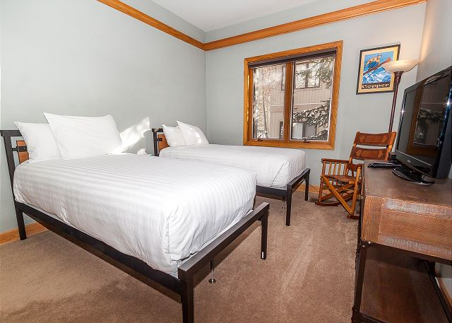 The guest bedroom features two twin-sized beds on our Ivory White Bedding program, a flat screen TV and an en suite bathroom.