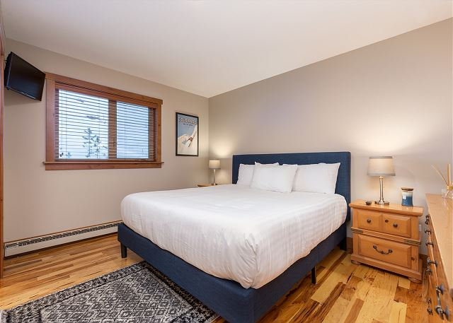The first master suite is on the main level and features a king-sized bed on our and a flat screen TV.