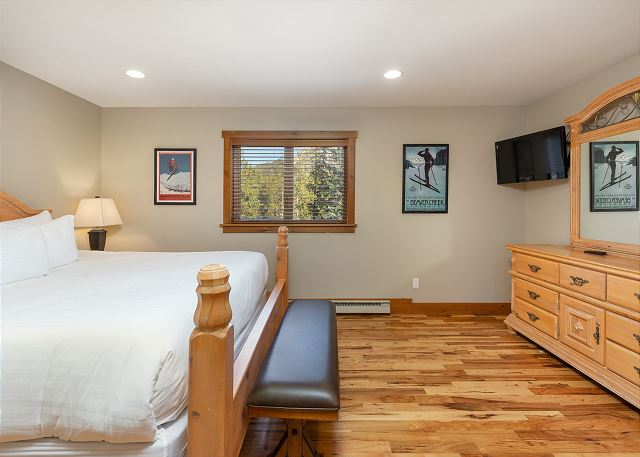 The first guest bedroom is on the main level and features a king-sized bed and a mounted flat screen TV.
