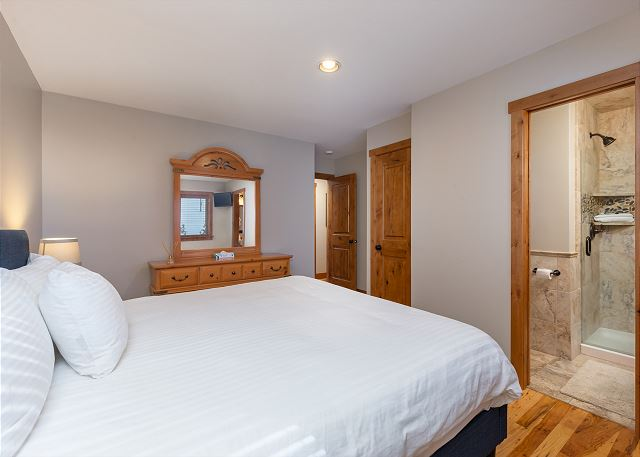 The first master suite is on the main level and features a king-sized bed and a flat screen TV.