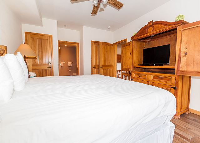 The first master suite is on the main level and features a king-sized bed with Ivory White Bedding, a flat screen TV and its own access to the balcony.
