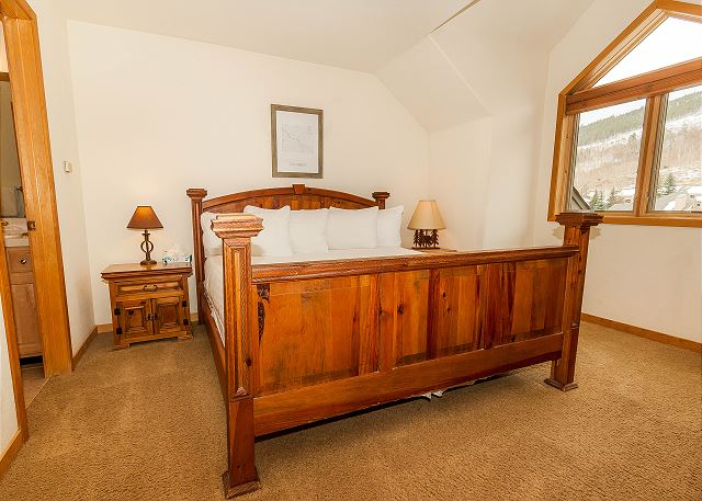 The second master suite is upstairs and features a king-sized bed with Ivory White Bedding.