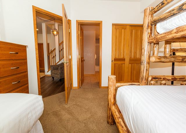 The guest bedroom is on the main level and features a twin bed and a twin-over-queen bunk bed with Ivory White Bedding.