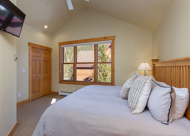 The first master suite is upstairs and features a king-sized bed and a mounted flat screen TV.