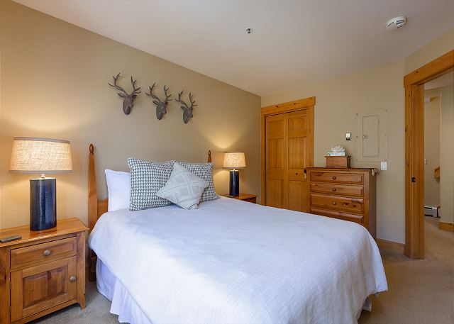 The second guest bedroom is downstairs and features a queen-sized bed and a mounted flat screen TV.