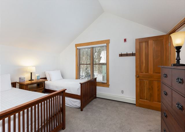 The guest bedroom features two twin-sized beds on our Ivory White Bedding and a flat screen TV.
