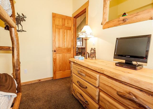 The second bedroom features a queen-sized bunk bed and a television.