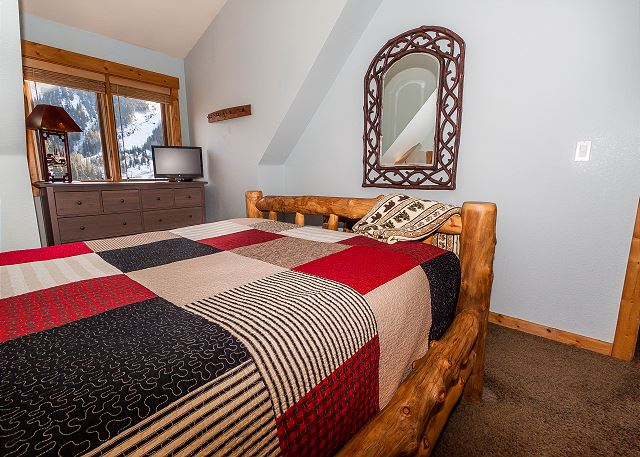 The first bedroom features a queen-sized bed, a flat screen TV and slope views.
