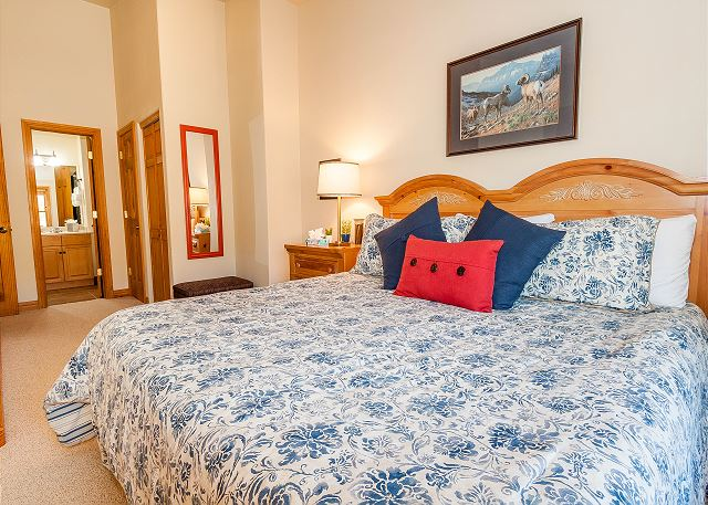 The second master suite features a king-sized bed and a mounted flat screen TV.