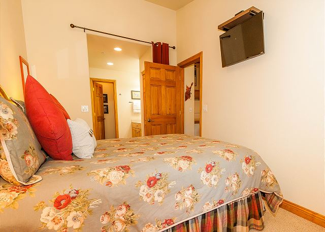 The first master suite features a queen-sized bed and a mounted flat screen TV.