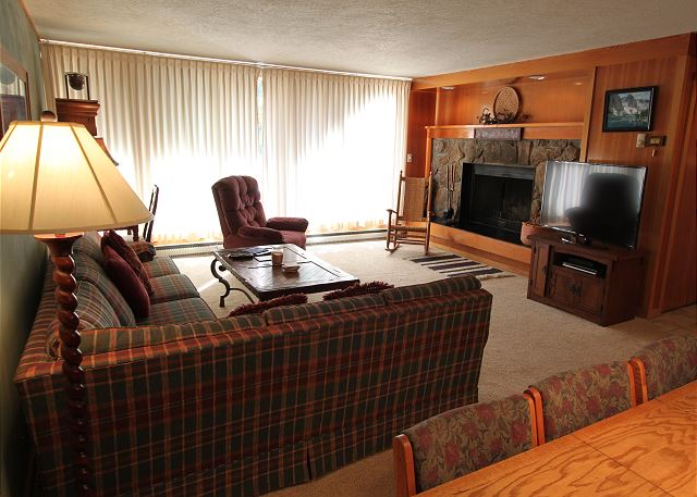 The living area features a wood-burning fireplace, flat screen TV and a queen-sized sleeper sofa.