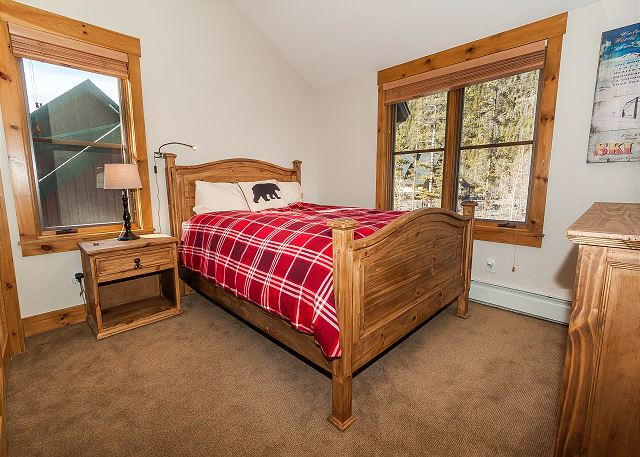 The first guest bedroom is upstairs and features a queen-sized bed and a mounted flat screen TV.