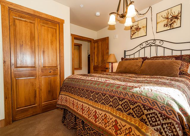 The first bedroom features a queen-sized bed and a flat screen TV.