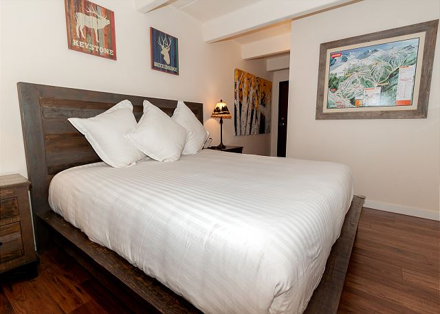 The master suite features a king-sized bed and a mounted flat screen TV.