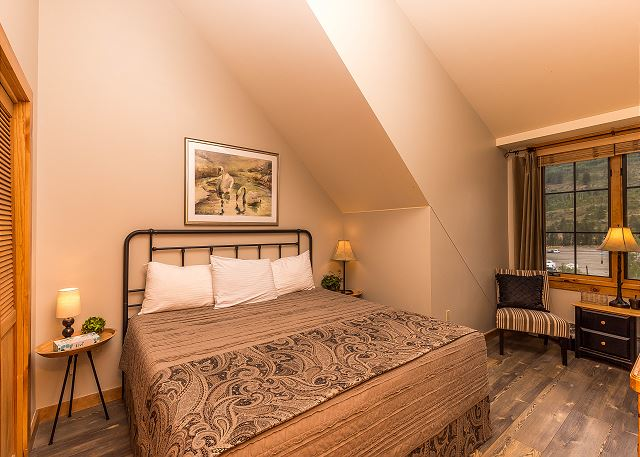 The bedroom features a king-sized bed, a flat screen TV and a seating area.
