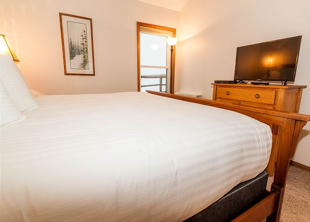 The master suite features a king-sized bed on our Ivory White Bedding program and a flat screen TV.
