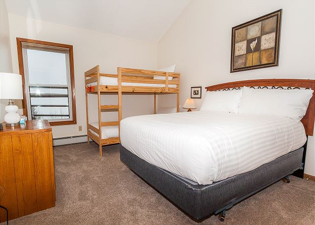 The guest bedroom features a queen-sized bed and a twin-sized bunk bed on our Ivory White Bedding program.