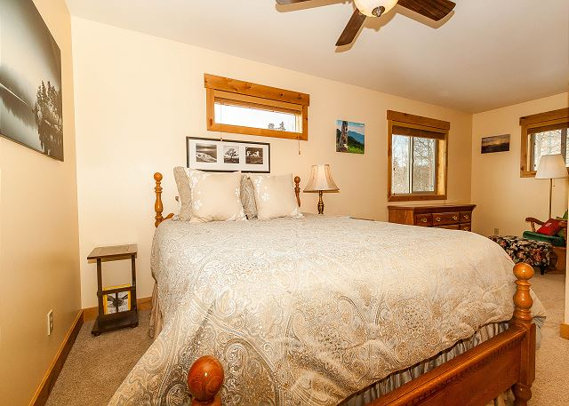 The master suite features a queen-sized bed, a flat screen TV and a seating area.