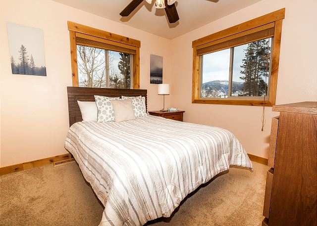 The first guest bedroom features a queen-sized bed, a flat screen TV and shares a bathroom with another bedroom.
