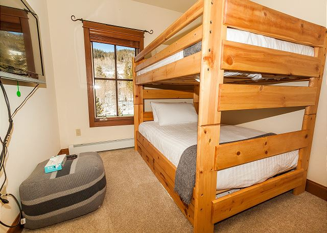 The guest bedroom features a full-sized bunk bed on our Ivory White Bedding program with a twin trundle and a mounted flat screen TV.