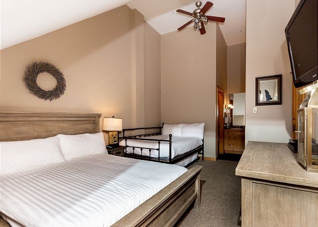 The second bedroom features a queen-sized bed and a full-sized bed on our Ivory White Bedding program with a twin trundle and a mounted flat screen TV.