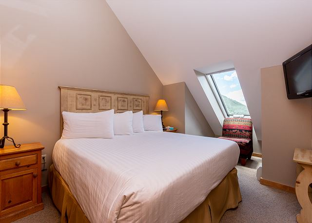 The first bedroom features a king-sized bed on our Ivory White Bedding program and a mounted flat screen TV.
