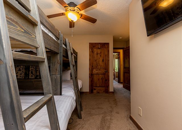 The second guest bedroom features two twin bunk beds and a mounted flat screen TV.