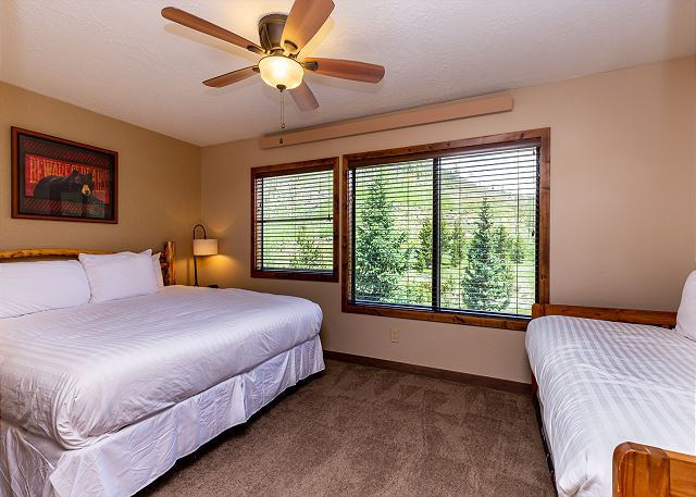 The first guest bedroom features a queen-sized bed, a twin day bed with twin trundle, and a mounted flat screen TV.
