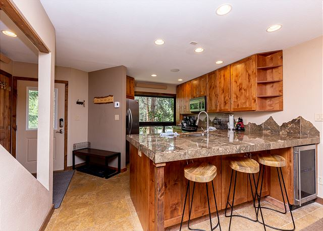 Breakfast bar with seating for three and a wine cooler.