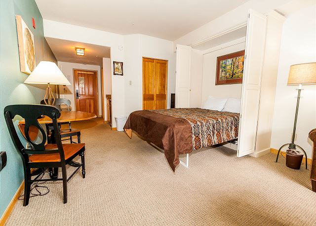 This studio features a living area with a queen Murphy bed, a queen sleeper sofa and a mounted flat screen TV.