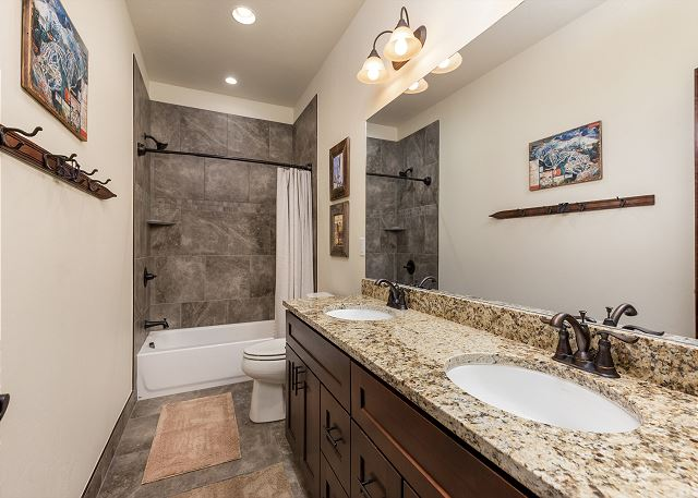 The lower level guest bathroom features a dual sink vanity and granite countertops.