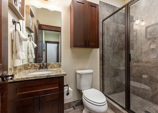 The upstairs guest bathroom is just outside the guest bedroom with a walk-in shower and granite countertops.