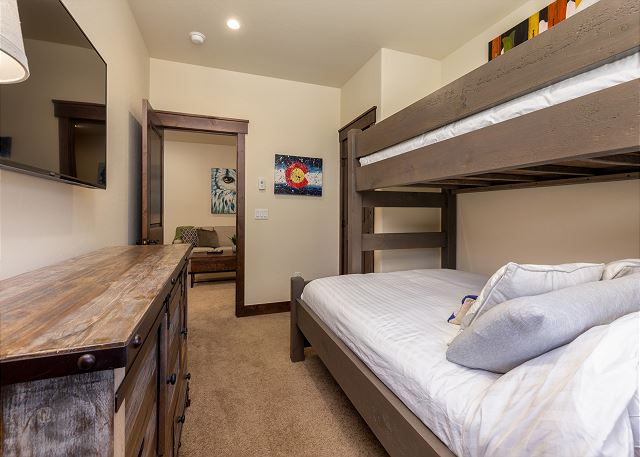 Lower level bunk room has a twin-xl over queen bunk and a flat screen tv.