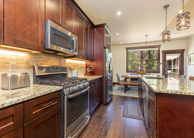 The fully stocked kitchen features granite countertops and stainless steel GE Profile appliances.