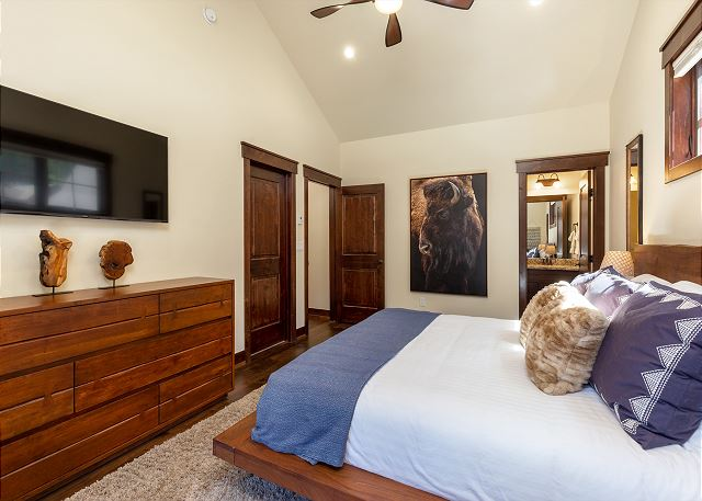 The master bedroom with a king-size bed facing a flat-screen TV and it also boasts a private balcony.