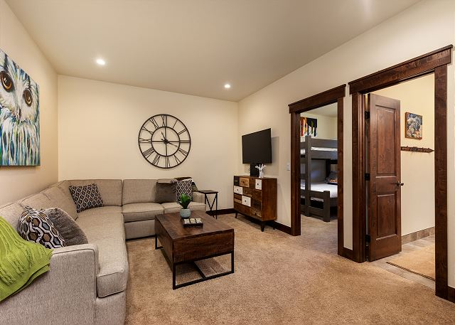 The secondary living room downstairs features a cozy sectional sofa for guests to enjoy a movie on the flat screen tv or family game night on the coffee table.