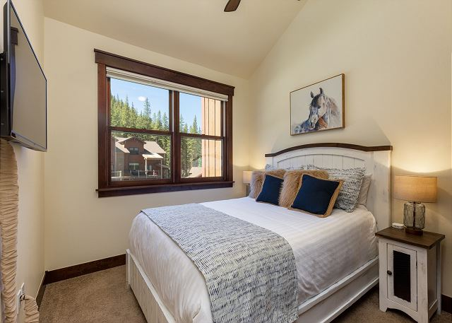 The upstairs guest bedroom features a beautiful queen bed, flat screen TV and a walk-in shower located in the hall bathroom just outside the bedroom.
