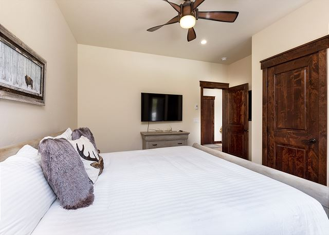 The downstairs guest bedroom features a king-size bed and flat screen TV, amazing forest views, and access to the lower patio.