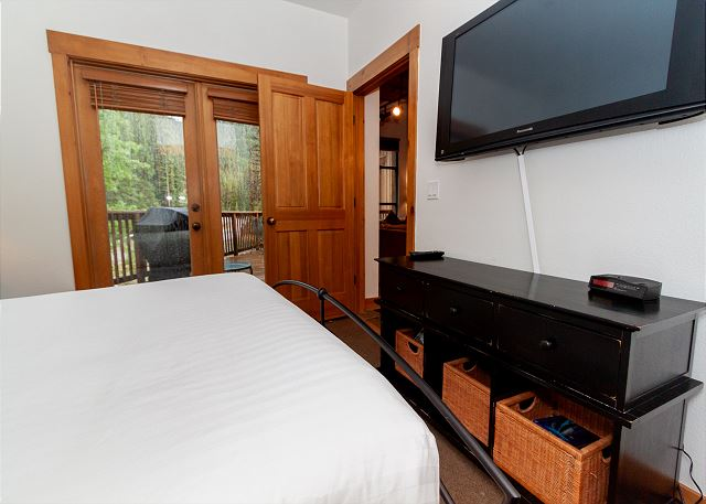 The downstairs guest bedroom features a queen bed and access to the private deck.